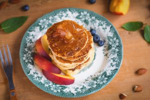 Pancakes with caramel apples, fresh peaches, blueberries and almonds on a colorful vintage plate. Healthy sweet breakfast. Vertical, toned image